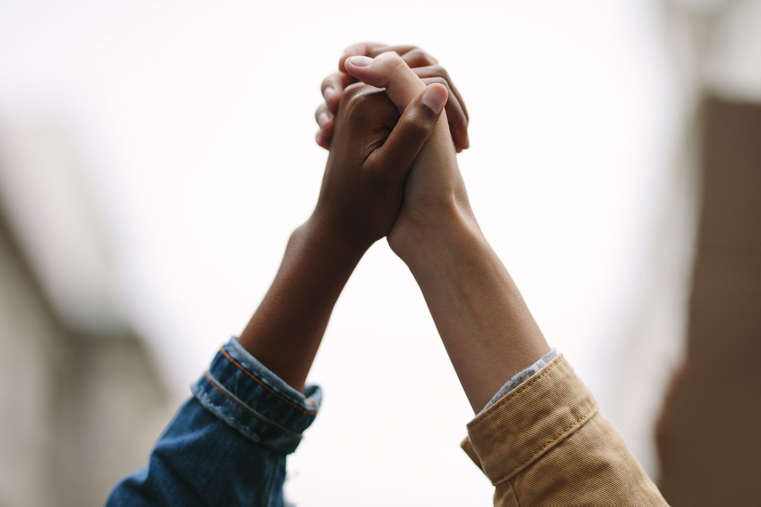Symbol of unity. Two women activists holding hands. Demonstrators protesting together holding hands.