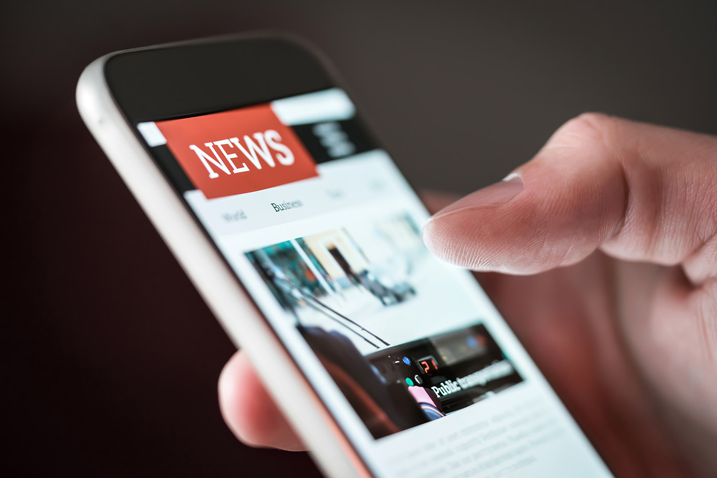 Mobile news application in smartphone. Man reading online news on website with cellphone. Person browsing latest articles on the internet. Light from phone screen.